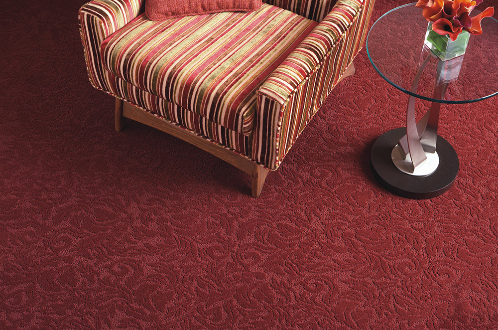 red textured carpet being displayed under a loveseat and glass table